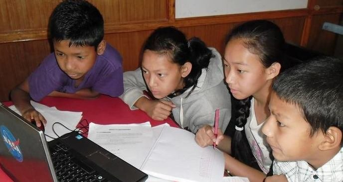 Image:  Four students solving problems in Nepal